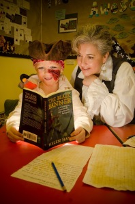 Author Helen Hart with a young boy reading her book The Black Banner