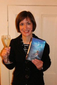 Photo of Jane with a copy of her book and a glass of champagne