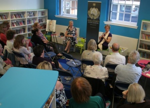 Alison talking to a group of readers, all seated, theatre-style